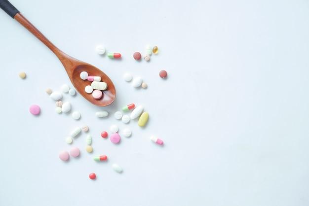 Bovenaanzicht van vele kleurrijke pillen en capsules op lepel op tafel