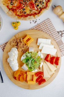 Bovenaanzicht van vele soorten kaas stukjes geserveerd op houten plaat
