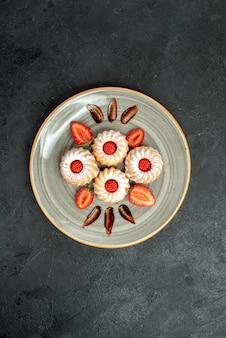 Bovenaanzicht van ver bord met koekjes witte plaat met koekjes met chocolade en aardbei in het midden van de tafel