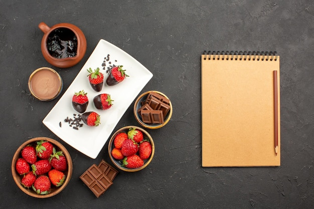 Bovenaanzicht van ver chocolade-aardbeienroomnotitieboekje en bruin potlood naast keukenbord met chocoladeroom en aardbeien met chocolade omhulde aardbeienchocolade