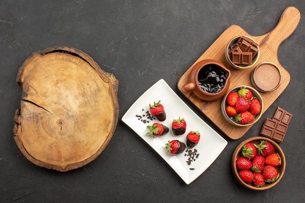 Bovenaanzicht van ver chocoladeaardbeien met chocolade omhulde aardbeien chocolade en keukenbord met chocoladeroom en aardbeien naast de snijplank