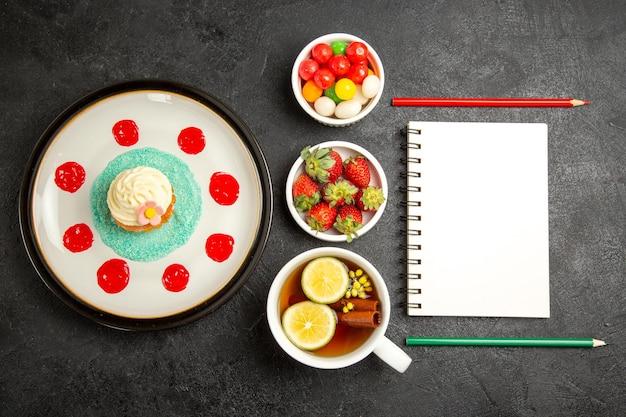Bovenaanzicht van ver cupcake een kopje thee plaat van cupcake kommen aardbeien en snoep naast het witte notitieboekje met twee potloden en het kopje thee met kaneelstokjes en citroen