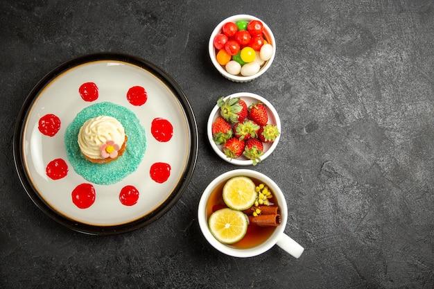 Bovenaanzicht van ver cupcake een kopje thee witte plaat van cupcake kommen aardbeien en snoep naast het kopje thee met kaneelstokjes en citroen