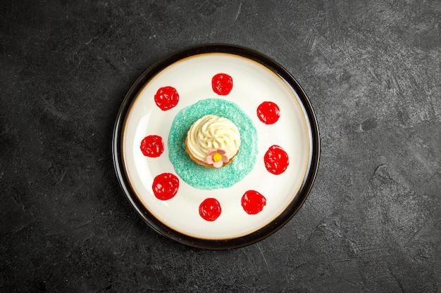 Bovenaanzicht van ver cupcake op het bord cupcake met saus op het witte bord in het midden van de donkere tafel