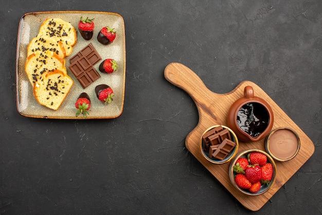 Bovenaanzicht van ver dessertbord van smakelijke cake met met chocolade omhulde aardbeien naast kommen chocoladeroom en bessen op de snijplank op de donkere tafel