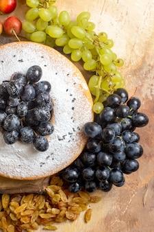 Bovenaanzicht van ver een cake een cake met zwarte druiven op het bord rozijnen kersen trossen druiven
