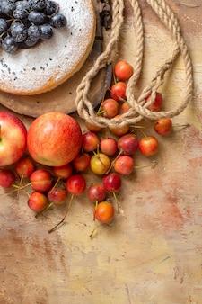 Bovenaanzicht van ver een cake een cake op het houten bord de smakelijke appels bessen touw