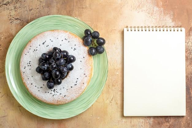 Bovenaanzicht van ver een cake een smakelijke cake met druiven witte notebook