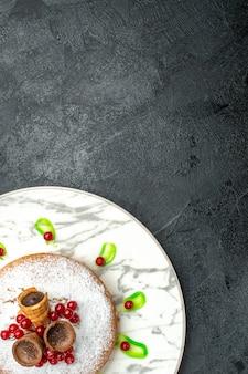 Bovenaanzicht van ver een cake grijze plaat van een cake met wafels bessen poedersuiker