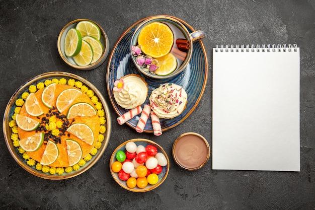 Bovenaanzicht van ver een kopje kruidenthee cupcakes met room en het kopje kruidenthee op de blauwe schotel naast het witte notitieboekje en kommen met citrusvruchten chocoladeroom en snoepjes op tafel