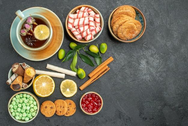 Bovenaanzicht van ver een kopje thee een kopje kruidenthee met citroenkoekjes snoepjes wafels kaneel