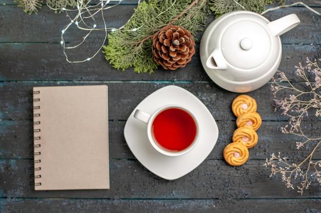 Bovenaanzicht van ver een kopje thee een kopje thee naast de witte notitieboekjetheepot en boomtakken op de donkere tafel