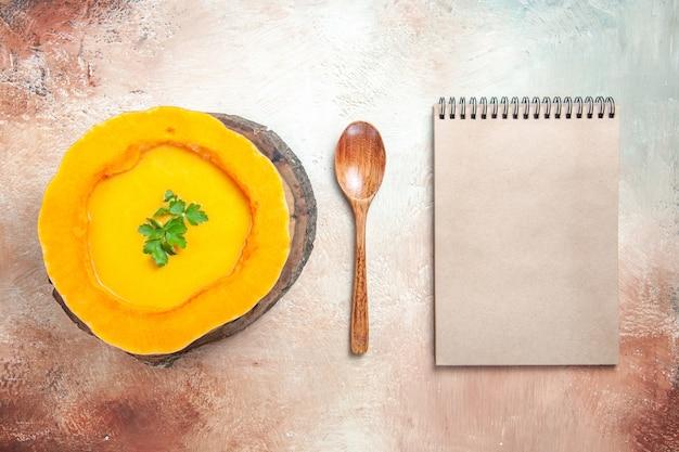 Bovenaanzicht van ver een soep, pompoensoep op het bord naast het notitieboekje van de lepelroom