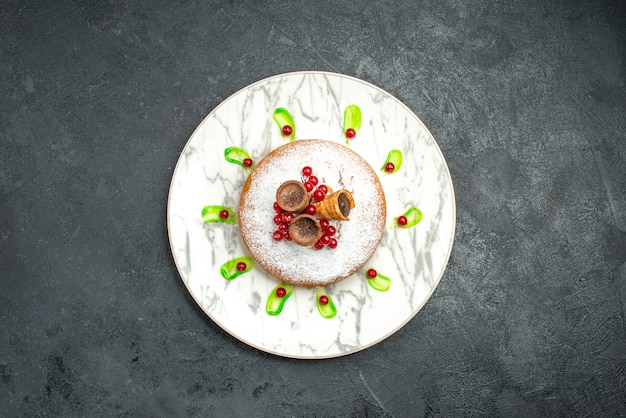Bovenaanzicht van ver een taart plaat van een smakelijke cake met poedersuiker wafels bessen