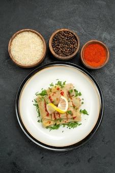 Bovenaanzicht van ver eten en kruiden gevulde kool met kruiden citroen en saus en kommen rijst kleurrijke kruiden en zwarte peper op donkere tafel