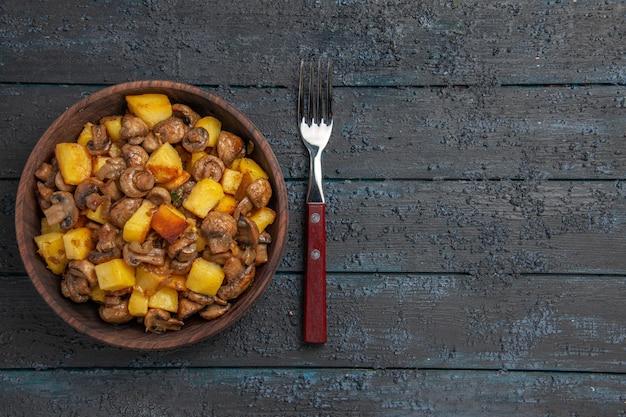 Bovenaanzicht van ver eten in de kom smakelijke aardappelen en champignons in de kom naast de vork aan de linkerkant van de donkere tafel