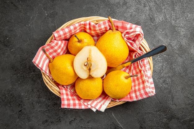 Bovenaanzicht van ver fruit in de mand gele peren met mes op het geruite tafelkleed in de mand op de donkere tafel