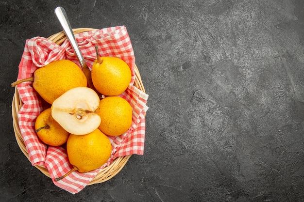 Bovenaanzicht van ver fruit in de mand houten mand met perenmes en geruit tafelkleed aan de linkerkant van de donkere tafel