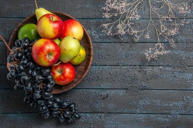 Bovenaanzicht van ver fruit in komkom met druiven peren appels limoenen naast boomtakken op donkere tafel