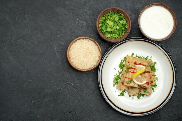 Bovenaanzicht van ver gevulde kool smakelijke gevulde kool met kruiden, citroen en saus op witte plaat en kommen met rijstkruiden en zure room aan de rechterkant van zwarte tafel