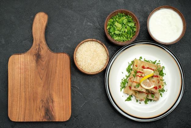 Bovenaanzicht van ver gevulde kool smakelijke gevulde kool met kruiden, citroen en saus op witte plaat en kommen met rijstkruiden en zure room naast een houten snijplank op zwarte tafel