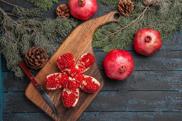 Bovenaanzicht van ver granaatappel aan boord van rode gepilde granaatappel op snijplank naast rijpe drie granaatappels mes en vuren takken met kegels op tafel