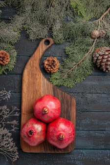 Bovenaanzicht van ver granaatappels aan boord granaatappels op het keukenbord en takken met kegels