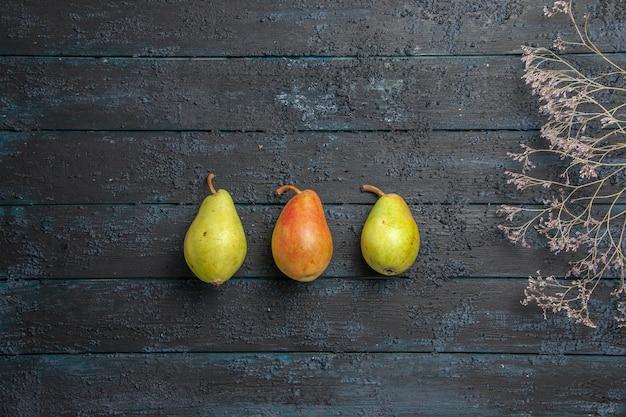 Bovenaanzicht van ver groen-geel-rode peren twee groene peren en een rood-gele peer in het midden van grijze tafel naast de boomtakken