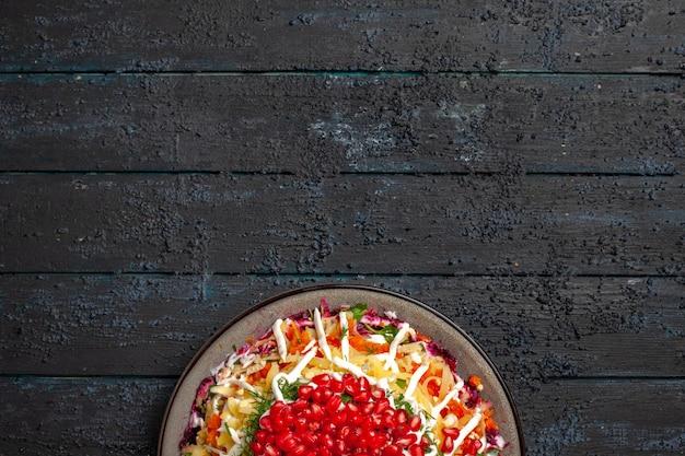 Bovenaanzicht van ver kersteten kerstgerecht met granaatappel in de plaat op de donkere achtergrond