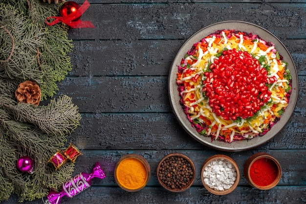Bovenaanzicht van ver kerstvoedsel kerstschotel met granaatappelkommen met kruiden en vuren takken met kerstboomspeelgoed