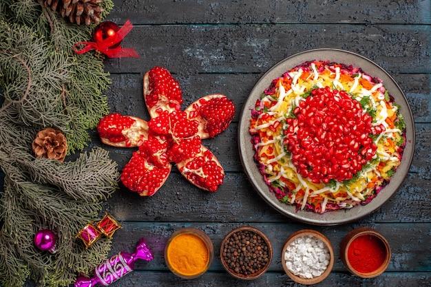 Bovenaanzicht van ver kerstvoedsel kerstschotel met granaatappelkommen met kruiden gepilde granaatappel en vuren takken met kerstboomspeelgoed