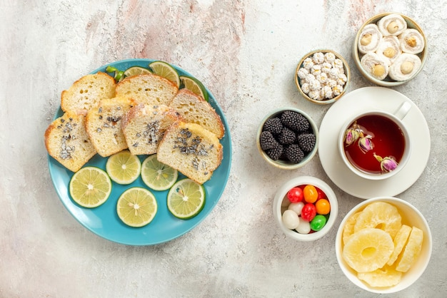 Bovenaanzicht van ver kopje thee plaat van cake en gesneden limoenen naast de kommen van verschillende snoepjes gedroogde ananas turks fruit en kopje thee op de witte achtergrond