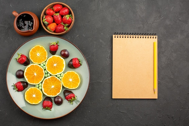 Bovenaanzicht van ver sinaasappel- en chocoladechocoladesaus en aardbeien naast met chocolade bedekte aardbei, gehakte oranje groene snoepjes en notitieboekje met potlood