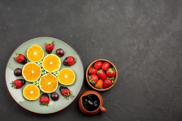 Bovenaanzicht van ver sinaasappel- en chocoladekommen met chocoladesaus en aardbeien en bord met gehakte oranje chocolade-bedekte aardbeiengroene snoepjes aan de linkerkant van de donkere tafel