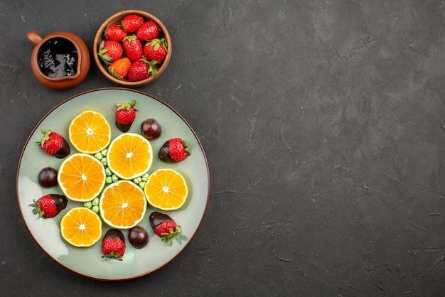 Bovenaanzicht van ver sinaasappel- en chocoladekommen met chocoladesaus en aardbeien naast een bord met met chocolade omhulde aardbeien, gehakte oranje groene snoepjes aan de linkerkant van de donkere tafel