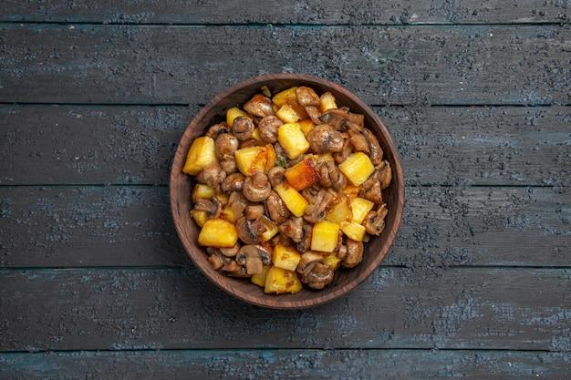 Bovenaanzicht van veraf bord met etensbruin bord met champignons en aardappelen op de grijze tafel