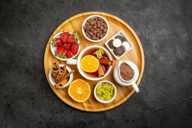 Bovenaanzicht van veraf bord met snoep houten bord met snoepjes citroen kaneelstokjes en een kopje thee met citroen