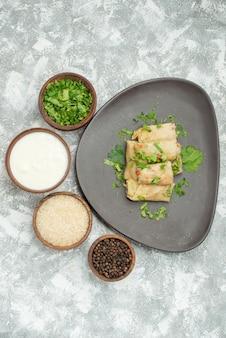 Bovenaanzicht van veraf bord met voedselkommen van kruiden, zure roomrijst en zwarte peper naast een grijze plaat met gevulde kool op tafel