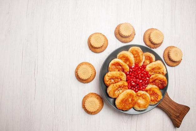 Bovenaanzicht van veraf bord op het bord koekjes en bord met smakelijke pannenkoeken en granaatappel op de houten snijplank op tafel