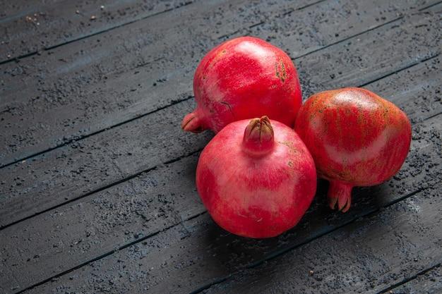 Bovenaanzicht van veraf drie granaatappels drie rijpe granaatappels op donkere tafel