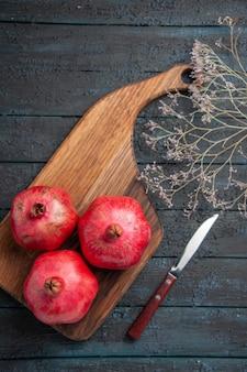 Bovenaanzicht van veraf drie granaatappels granaatappels op snijplank naast mes en boomtakken