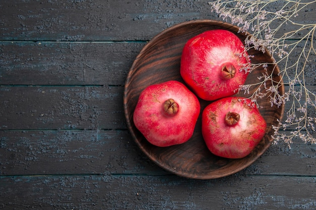 Bovenaanzicht van veraf drie granaatappels houten kom granaatappels naast de takken op grijze tafel