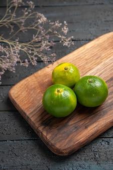 Bovenaanzicht van veraf drie limoenen drie limoenen op keukenbord op tafel naast de takken