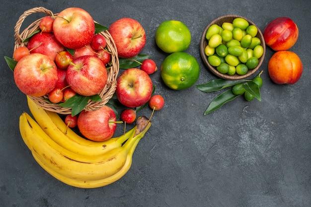 Bovenaanzicht van veraf fruit, bananen, nectarines, citrusvruchten, mandarijnen, mand met appels, kersen