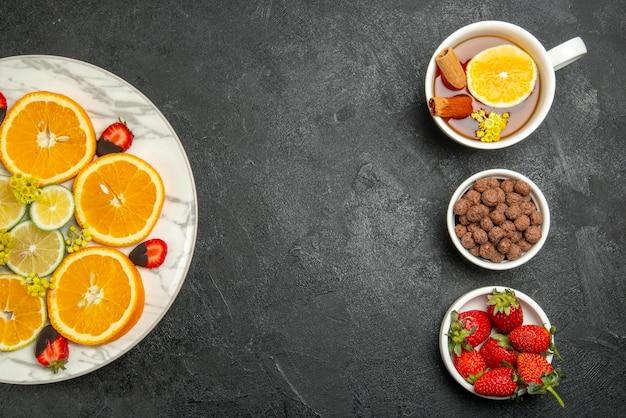 Bovenaanzicht van veraf gesneden oranje bord van gesneden sinaasappel-citroen met chocolade bedekte aardbeien naast het kopje thee, hazelnoten en aardbeien