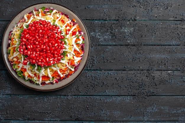Bovenaanzicht van veraf kerstschotel kerstsalade in het bord aan de linkerkant van de tafel