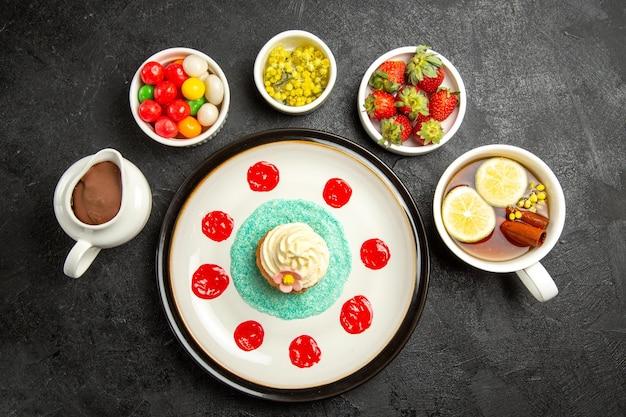 Bovenaanzicht van veraf smakelijk dessertbord van smakelijke cupcake de kommen met chocoladeroomsnoepjes en aardbeien en een kopje thee met citroen