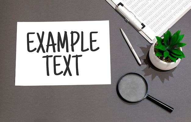 Bovenaanzicht van vergrootglas, zonnebril, rekenmachine, pen, plant en notitieboekje geschreven met cut cost.