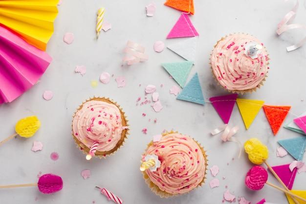 Bovenaanzicht van verjaardag cupcakes met aangestoken kaarsen
