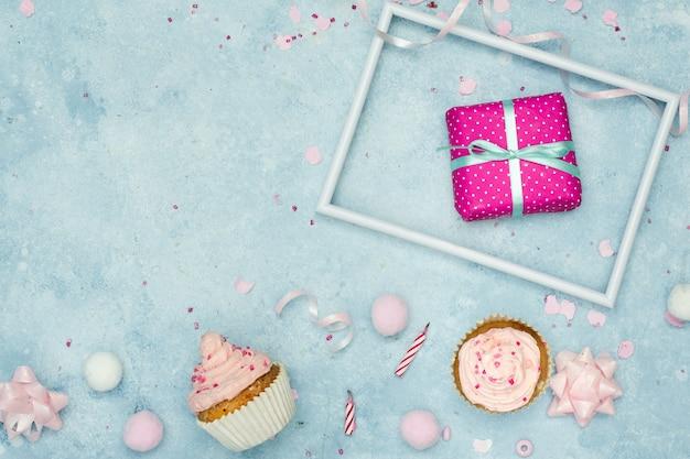 Bovenaanzicht van verjaardagscadeau met cupcakes en kopie ruimte